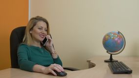 Business woman talking by mobile phone sitting on desk in travel company office. Woman manager calling on smartphone in tourist agency close up stock video footage