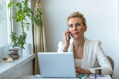 Business woman talking on mobile phone while sitting with a laptop computer Stock Photos