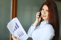 Business woman talking on mobile phone, smiling and looking at camera. Shallow depth of field. royalty free stock image