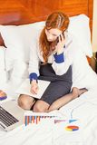 Business woman talking on mobile phone working on laptop in hotel room Royalty Free Stock Image