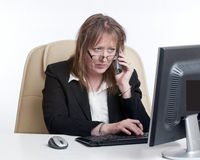 Business woman talking on phone. A business woman talking whilst working on her computer Royalty Free Stock Image