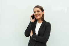 Business woman talking by phone against the glass wall in the ci Stock Images
