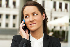 Business woman talking by phone against the glass wall in the ci Royalty Free Stock Photos