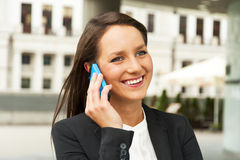 Business woman talking by phone against the glass wall in the ci Royalty Free Stock Photography