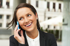 Business woman talking by phone against the glass wall in the ci Stock Image