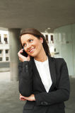 Business woman talking by phone against the glass wall in the ci Royalty Free Stock Photo