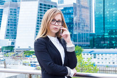Business woman talking on the phone on the background of skyscrapers Stock Photography