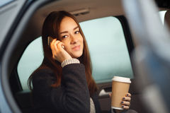 Business woman talking on phone with coffee sitting inside car Royalty Free Stock Image