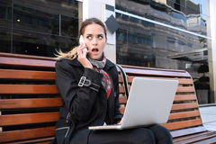 Business woman talking on the phone with her laptop. Royalty Free Stock Image
