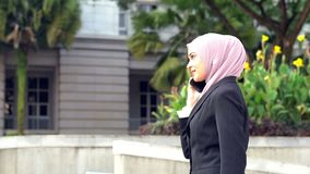 Business woman talking on the phone. Muslim business woman talking on the phone while walking stock video