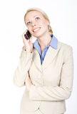 Business woman talking on the phone. Over white. Business woman talking on the phone, looking up. Over white background. Formal wear Royalty Free Stock Photos