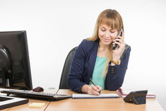 Business woman talking on the phone records in a notebook date business meeting Royalty Free Stock Photos
