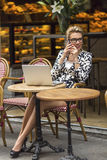Business woman talking on the phone sitting in outdoors cafe with laptop. Royalty Free Stock Photos