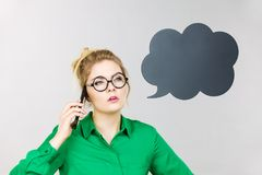 Business woman talking on phone with thinking bubble. Confused business woman wearing green shirt and red eyeglasses talking on phone with black thinking or Royalty Free Stock Images