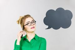 Business woman talking on phone with thinking bubble. Confused business woman wearing green shirt and red eyeglasses talking on phone with black thinking or Stock Image