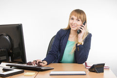 Business woman talking on the phone and working on the computer Royalty Free Stock Images
