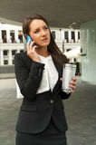 Business woman talking by smartphone, with caffee cup Royalty Free Stock Image