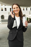 Business woman talking by smartphone, with caffee cup and newspap Stock Image