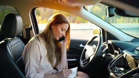 Business woman talking on a smartphone and taking notes in the daily sitting in the car. Young business woman talking on a smartphone and taking notes in the stock footage