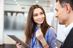Business woman talking to her client and using tablet Stock Images