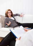Business woman talking to his psychiatrist explaining something Stock Image