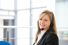 Business woman talking using her headset in the office Royalty Free Stock Photography