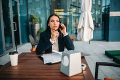 Business woman talks by mobile phone in cafe. Modern building, financial center, cityscape. Female businessperson in suit Royalty Free Stock Photo