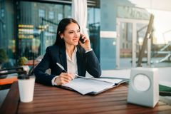 Business woman talks by mobile phone in cafe. Modern building, financial center, cityscape. Female businessperson in suit Royalty Free Stock Image