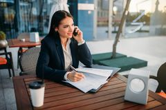 Business woman talks by mobile phone in cafe. Modern building, financial center, cityscape. Female businessperson in suit Stock Photography