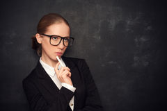 Business woman teacher with glasses  and chalk. Business woman teacher with glasses and a suit with chalk   the lost in thought at a school board Royalty Free Stock Images