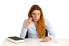 Business woman teacher with glasses skeptically looking through magnifying glass Royalty Free Stock Photography