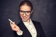 Business woman teacher with glasses and a suit with chalk   at a. Business woman teacher with glasses and a suit with chalk   the lost in thought at a school Royalty Free Stock Photo
