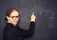 Business woman teacher with glasses and a suit with chalk. The lost in thought at a school board Royalty Free Stock Photos