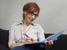 BUSINESS WOMAN OR TEACHER WORKING AT HOME ON COUCH Stock Photos