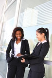 Business Woman Team. Two interracial (african and asian) business women team at office building Stock Photography