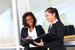Business Woman Team. Two interracial (african and asian) business women team at office building