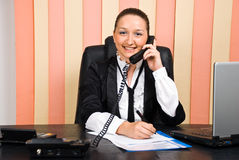 Business woman by telephone taking notes. Young business woman talking by telephone and taking notes,check also Business people Royalty Free Stock Photography
