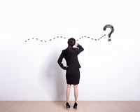 Business woman think. Back view of business woman look and think about complicated questions. Drawn question marks on the white wall royalty free stock photo