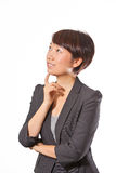 Business woman thinking. Isolated smiling business woman(Asian/Chinese/yellow race) is thinking in white background. It seem like she has got an idea Royalty Free Stock Photo