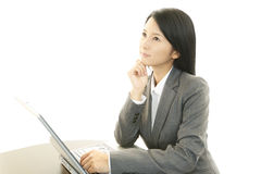 Business Woman Thinking. Asian business woman sitting at desk working on laptop Royalty Free Stock Photo