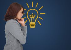 Business woman thinking against blue background with yellow lightbulb Stock Images