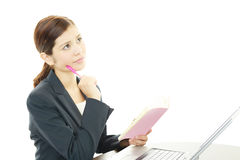 Business Woman Thinking. Asian business woman sitting at desk working on laptop Stock Images