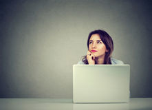 Business woman thinking daydreaming sitting at desk with laptop computer