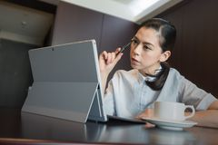 Business woman thinking new idea work plan, hold pen on hand. sitting using tablet Laptop Computer Stock Image