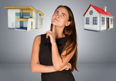 Business woman thinking over house and cottage Royalty Free Stock Photos