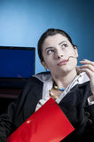 Business woman thinking at a problem. Young business woman disturbed from reading a red file, thinking how to solve a problem, focus selected on the face Stock Image