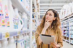 Business woman is thinking about shopping with a tablet selects household chemicals in a supermarket. Business woman is thinking about shopping with a tablet in Royalty Free Stock Photos