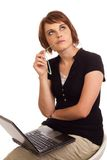 Business woman thinking while working on laptop. Young adult Caucasian business woman thinking about a problem whilst working on her laptop Royalty Free Stock Image