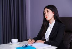 Business woman thinking and writes a note on the notebook Stock Photography