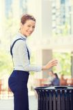 Business woman throwing empty paper coffee cup in recycling bin. Portrait business woman throwing empty paper coffee cup in recycling bin, isolated outside sunny royalty free stock image